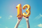 A gold foil number 13 balloon is held high in the air by caucasian male hand.  The image has been taken outdoors on a bright sunny day, the sky is blue with some clouds. A vintage style effects has be