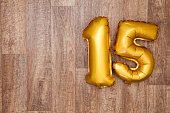 A gold foil number 15 balloon on a wooden background. The number is made from shiny golden foil and is inflated, it is on the right hand side of the image leaving copy space on the left of the image f