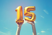 A gold foil number 15 balloon is held high in the air by caucasian male hand.  The image has been taken outdoors on a bright sunny day, the sky is blue with some clouds. A vintage style effects has be