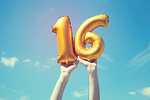 A gold foil number 16 balloon is held high in the air by caucasian male hand.  The image has been taken outdoors on a bright sunny day, the sky is blue with some clouds. A vintage style effects has be
