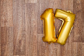 A gold foil number 17 balloon on a wooden background. The number is made from shiny golden foil and is inflated, it is on the right hand side of the image leaving copy space on the left of the image f