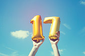 A gold foil number 17 balloon is held high in the air by caucasian male hand.  The image has been taken outdoors on a bright sunny day, the sky is blue with some clouds. A vintage style effects has be