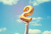A gold foil number 2 balloon is held high in the air by caucasian male hand.  The image has been taken outdoors on a bright sunny day, the sky is blue with some clouds. A vintage style effects has bee