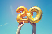 A gold foil number 20 balloon is held high in the air by caucasian male hand.  The image has been taken outdoors on a bright sunny day, the sky is blue with some clouds. A vintage style effects has be