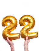 Gold foil number 22 balloons held by a caucasian male hand. The numbers are being held at the base. The numbers are made from shiny golden foil and is inflated. The background is plain white.