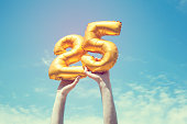 A gold foil number 25 balloon is held high in the air by caucasian male hand.  The image has been taken outdoors on a bright sunny day, the sky is blue with some clouds. A vintage style effects has be