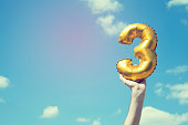 A gold foil number 3 balloon is held high in the air by caucasian male hand.  The image has been taken outdoors on a bright sunny day, the sky is blue with some clouds. A vintage style effects has bee