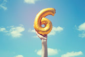 A gold foil number 6 balloon is held high in the air by caucasian male hand.  The image has been taken outdoors on a bright sunny day, the sky is blue with some clouds. A vintage style effects has bee