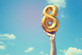 A gold foil number 8 balloon is held high in the air by caucasian male hand.  The image has been taken outdoors on a bright sunny day, the sky is blue with some clouds. A vintage style effects has bee
