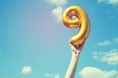 A gold foil number 9 balloon is held high in the air by caucasian male hand.  The image has been taken outdoors on a bright sunny day, the sky is blue with some clouds. A vintage style effects has bee
