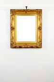 Gold Ornate Picture Frame Hanging From Rail On Wall