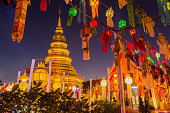 Gold pagoda and lantern hung up on the rail to the prosperity in loy kratong festival at wat phra that haripunchai lamphun Thailand at night time