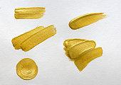 Gold brush stokes set on white textured paper background