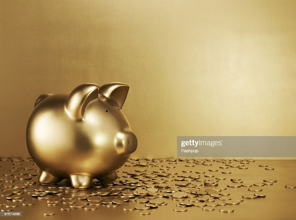 Gold piggy bank with gold coins : Stock Photo