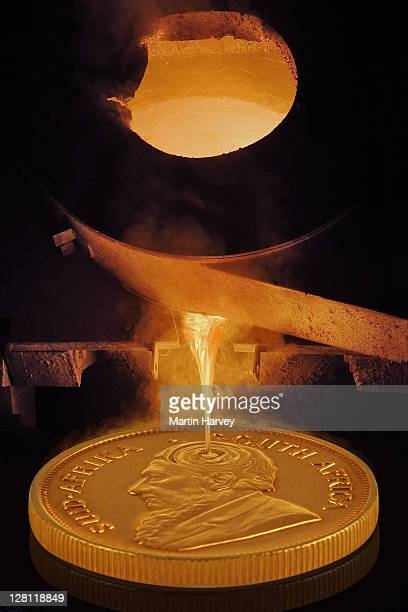 Gold pouring into gold Krugerrand coin, an alloy of 91.67 % pure gold and 8.33% copper, which gives the coins its orange tinge. (Digital Composite).