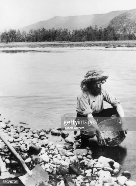 A gold prospector panning for alluvial gold in the Klondike a region in the western region of the Yukon Territory Canada circa 1898
