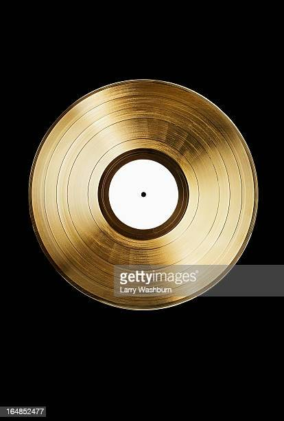 A gold record on a black background