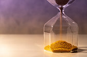 Gold sand running through the shape of modern hourglass on white table.Time passing and running out of time. Urgency countdown timer for business deadline concept