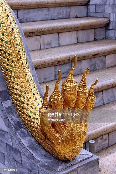 Gold sculpture snake and Buddha heads Bangkok Thailand