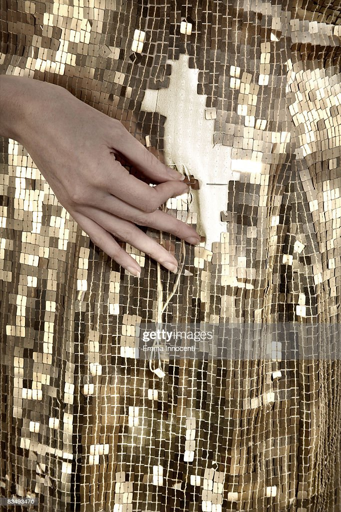 Gold sequin dress being mended : Stock Photo