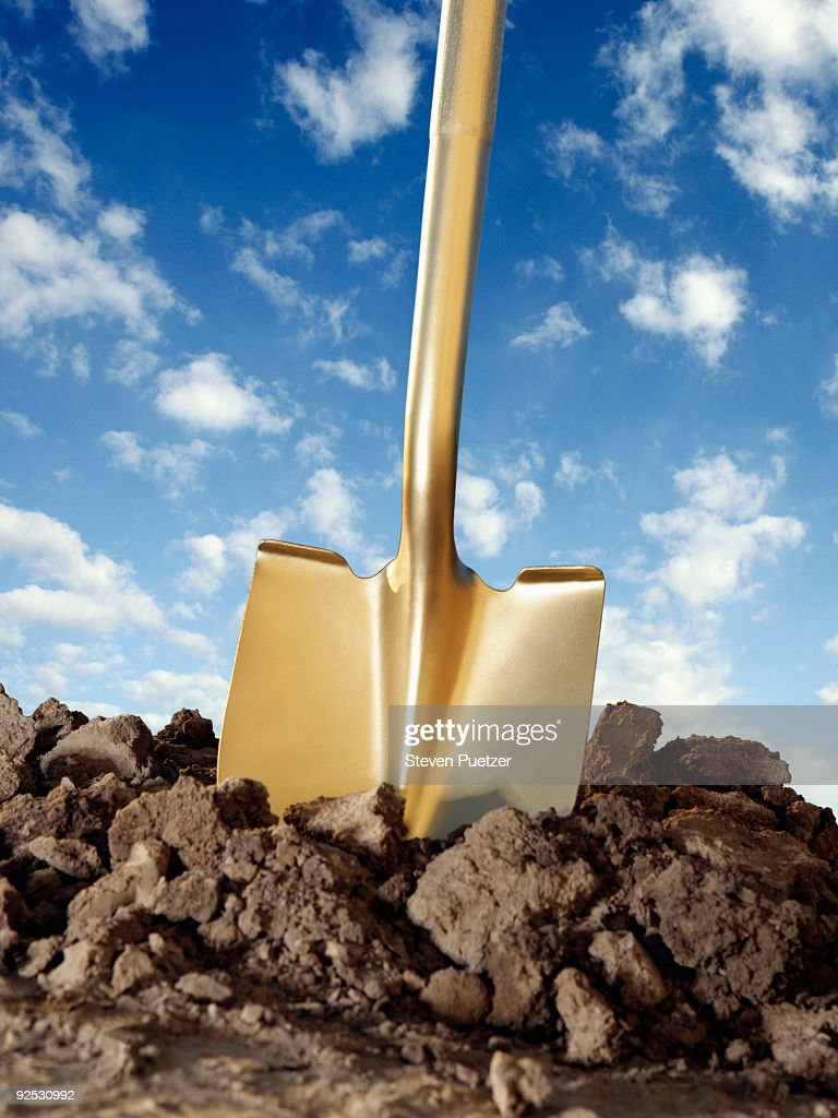 Gold shovel in freshly dug dirt with blue sky