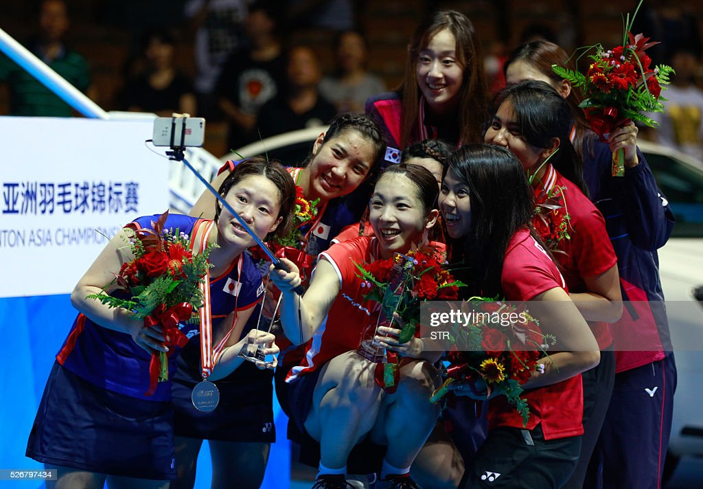 Gold, silver, and bronze medalists take photos with a selfie stick during the award ceremony of the women's doubles final at the 2016 Badminton Asia Championships in Wuhan, central China's Hubei province on May 1, 2016. / AFP / STR