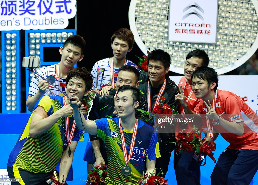 Gold, silver, and bronze medalists take photos with a selfie stick during the award ceremony of the men's doubles final at the 2016 Badminton Asia Championships in Wuhan, central China's Hubei province on May 1, 2016. / AFP / STR