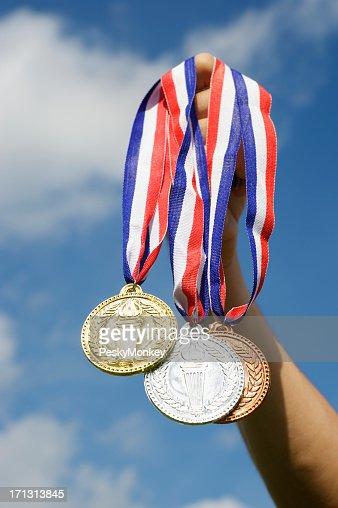 Gold Silber und Bronze Medaillen hängende Hand Holding Blue Sky