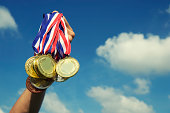 Gold Silver Bronze Medals Held Up in Blue Sky