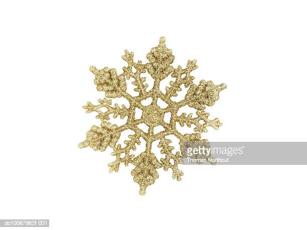 Gold snow flake ornament on white background