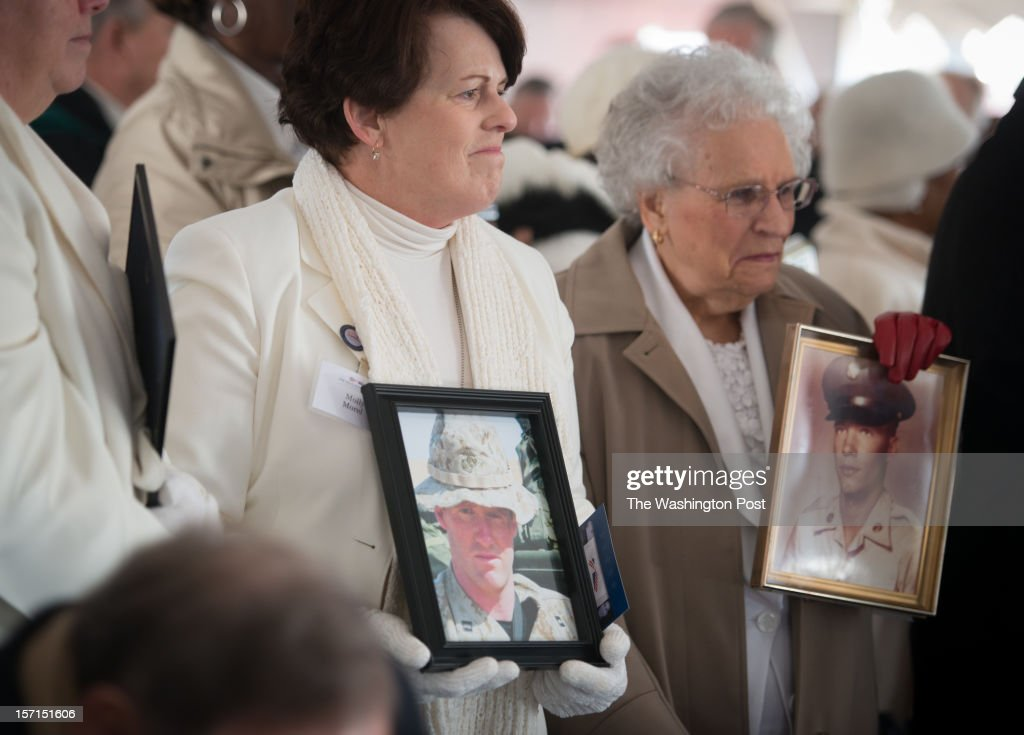 Gold Star mothers, Molly Morel, left of Martin, Tennessee, and Emogene Cupp, of Alexandria, Virginia stand with photos of their sons. On November 28, the Secretary of Defense, congressional leaders, veterans and Gold Star family members attended the ceremonial groundbreaking of The Education Center at The Vietnam Veterans Memorial.