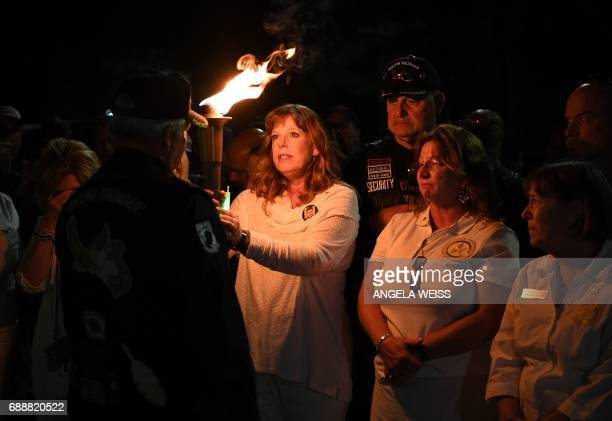 Gold Star Mothers who have lost a child in the US military and their supporters hold a torch as they recite the names of their children during a...