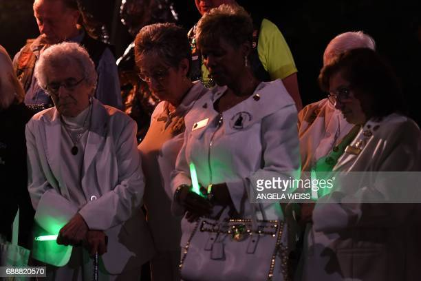 Gold Star Mothers who have lost a child in the US military and their supporters pray during a candlelight vigil near the Vietnam Veterans Memorial in...