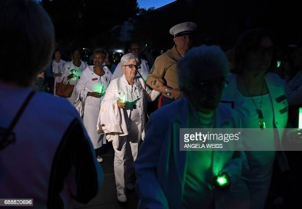 Gold Star Mothers who have lost a child in the US military and their supporters arrive for a candlelight vigil near the Vietnam Veterans Memorial in...