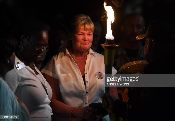 Gold Star Mothers who have lost a child in the US military and their supporters hold a torch as they say the name of their child during a candlelight...