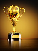 Football winner cup with golden soccer ball on yellow background
