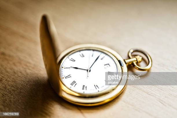 gold vintage pocket watch on wood table