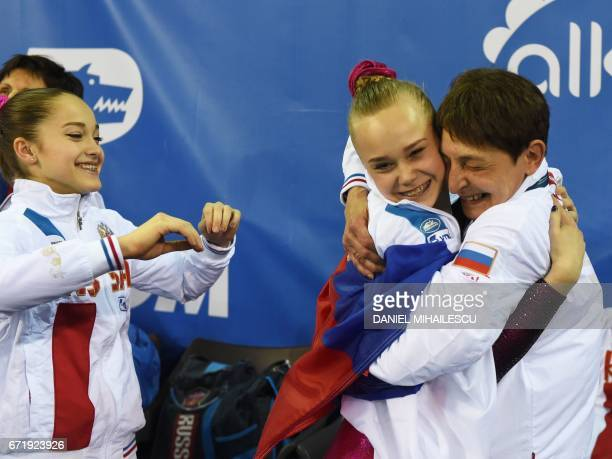 Gold winner Angelina Melnikova of Russia celebrates with team members after winning the women's floor event of the apparatus final at the European...