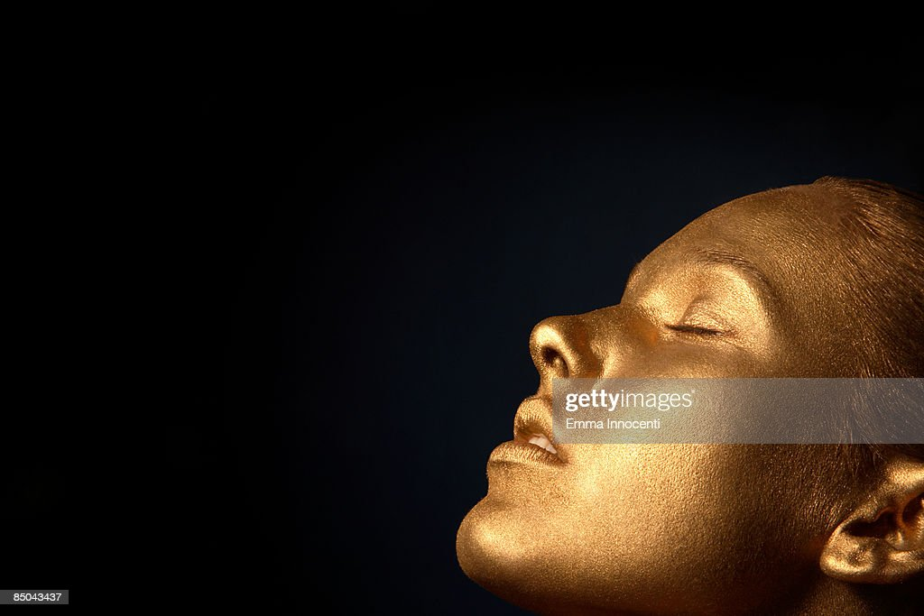Gold young woman  with eyes closed : Stock Photo