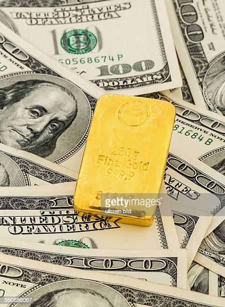 Goldbarren auf Dollarscheinen Symbolfoto für Goldreserven Wechselkurse Kapitalanlage Sicherheit