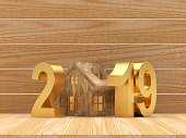 Real estate concept. Golden numbers 2019 New Year and wooden house icon on wooden background. 3D illustration