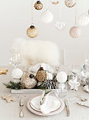 View of crystal and silver utensil on table set for New Year with shiny golden and silver baubles.