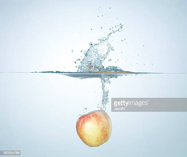 Golden apple splashing into water
