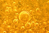 Golden background with big and small gold bubbles oil inside a gold liquid.