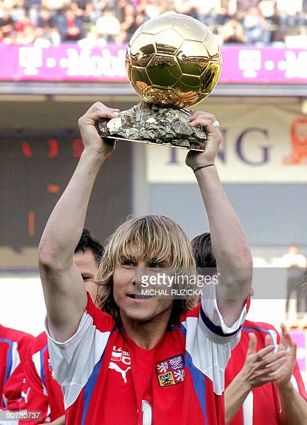 OUT== Golden Ball winner and the Czech Republic's player of the year for 2003 Pavel Nedved raises his trophy 28 April 2004 before international...