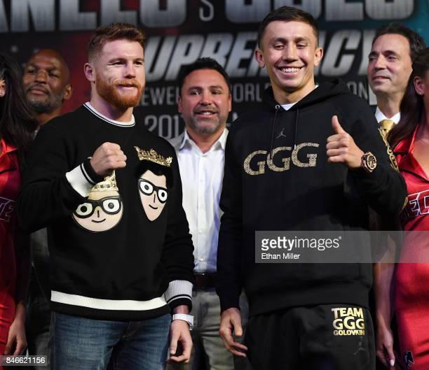 Golden Boy Promotions Chairman and CEO Oscar De La Hoya looks on as Canelo Alvarez and WBC WBA and IBF middleweight champion Gennady Golovkin pose...