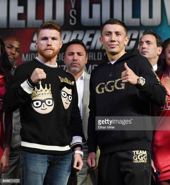 Golden Boy Promotions Chairman and CEO Oscar De La Hoya looks on as Canelo Alvarez and WBC WBA and IBF middleweight champion Gennady Golovkin pose...
