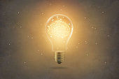 golden brain glowing inside of light bulb on paper texture background