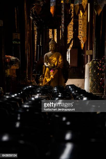 Golden buddha  statue with row of monk bowl