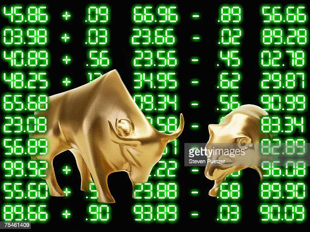 Golden bull and bear figurines against digitally generated numbers (digital composite)